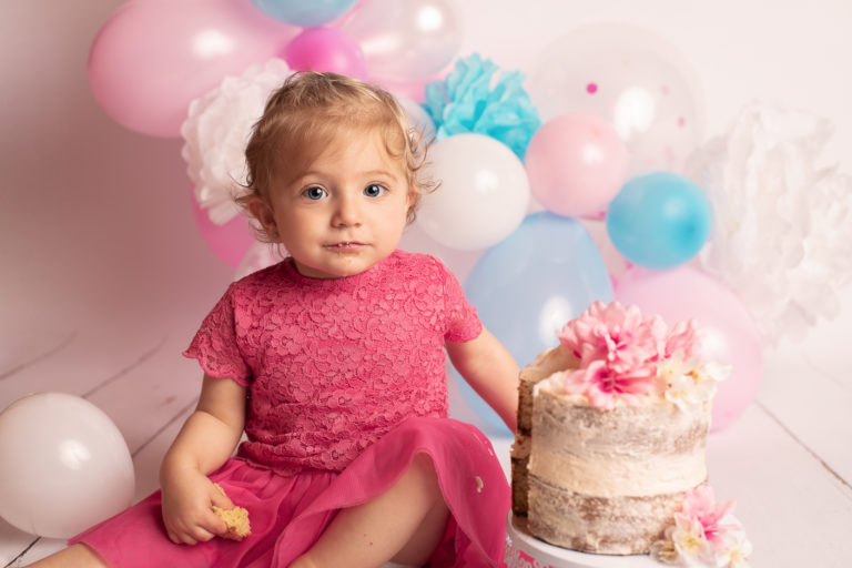 Petite fille d'un an avec un regard malicieux, un morceau de gâteau dans la main et de la crème autour de la bouche