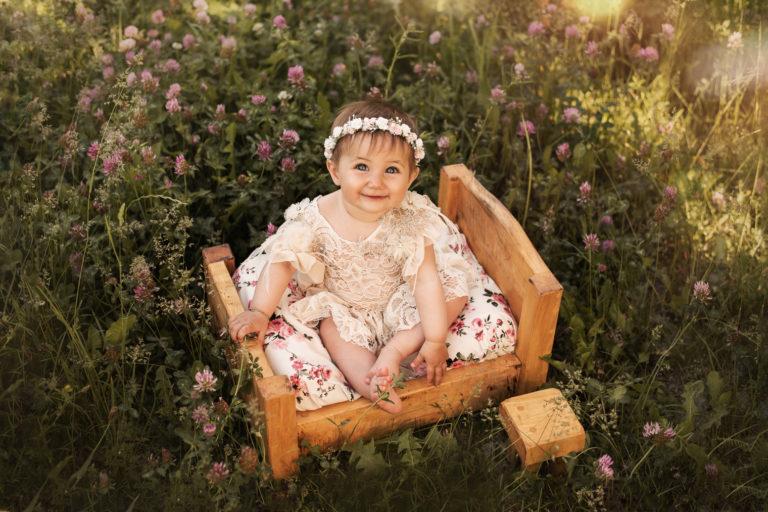 Bébé fille qui sourit, elle a une robe en dentelle, une couronne de fleurs et elle est assise sur un petit lit en bois au milieu d'un champ de fleurs de trèfle
