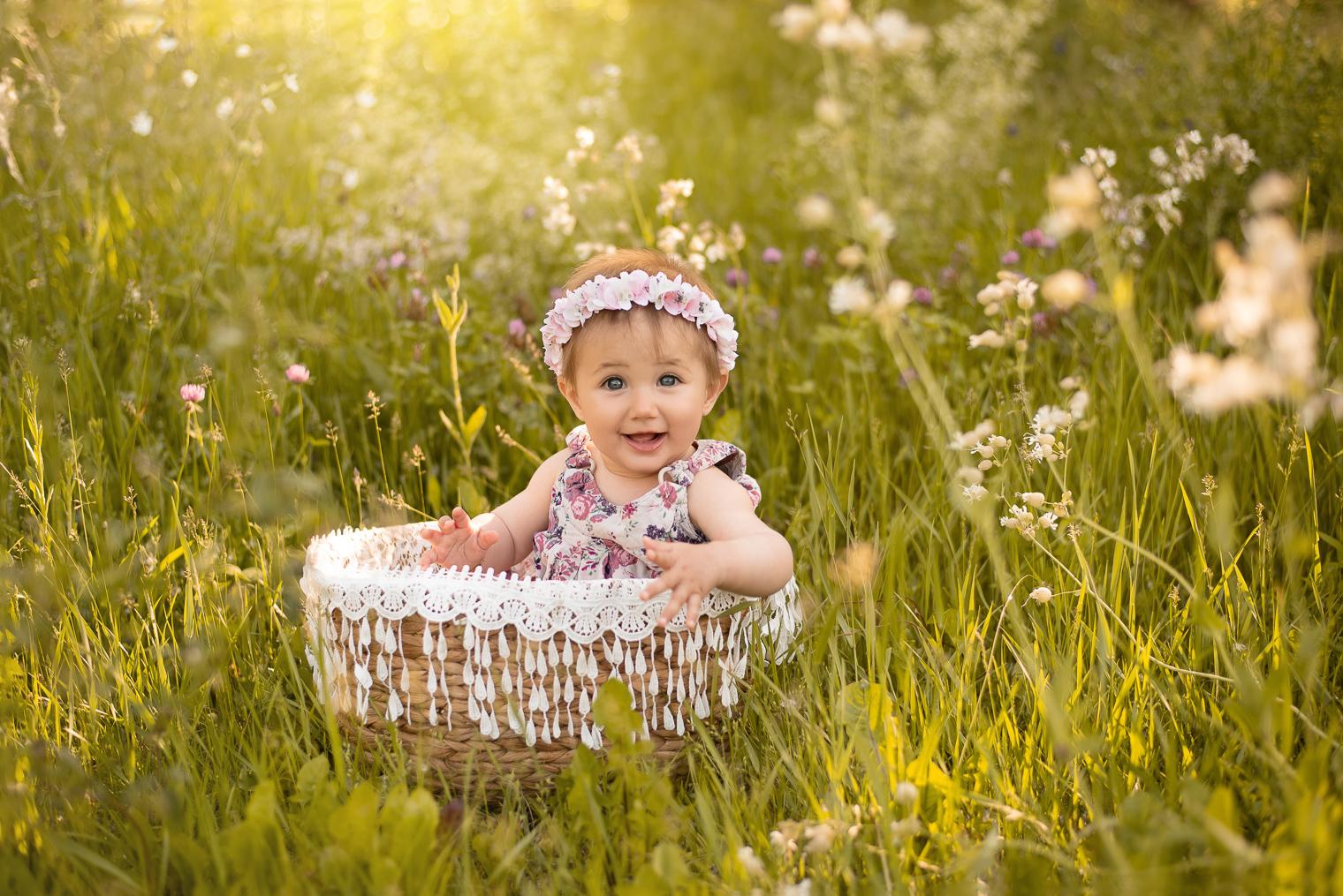 Bébé fille avec une robe à fleurs et une couronne de fleurs, assise dans un panier en osier dans un champ de fleurs