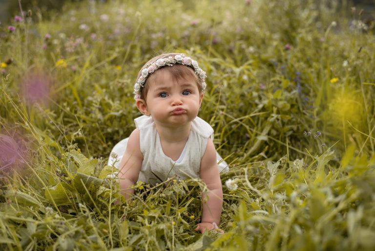 Bébé fille avec une robe blanche a pois doré et une couronne de fleurs, elle est à quatre patte dans l'herbe et fait une grimace