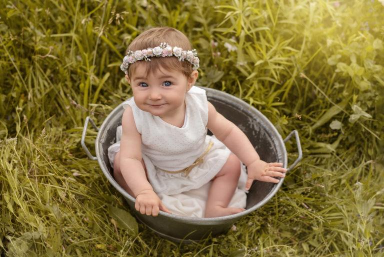 Bébé fille avec une robe blanche a pois doré et une couronne de fleurs, assise dans une bassine en métal dans un champ
