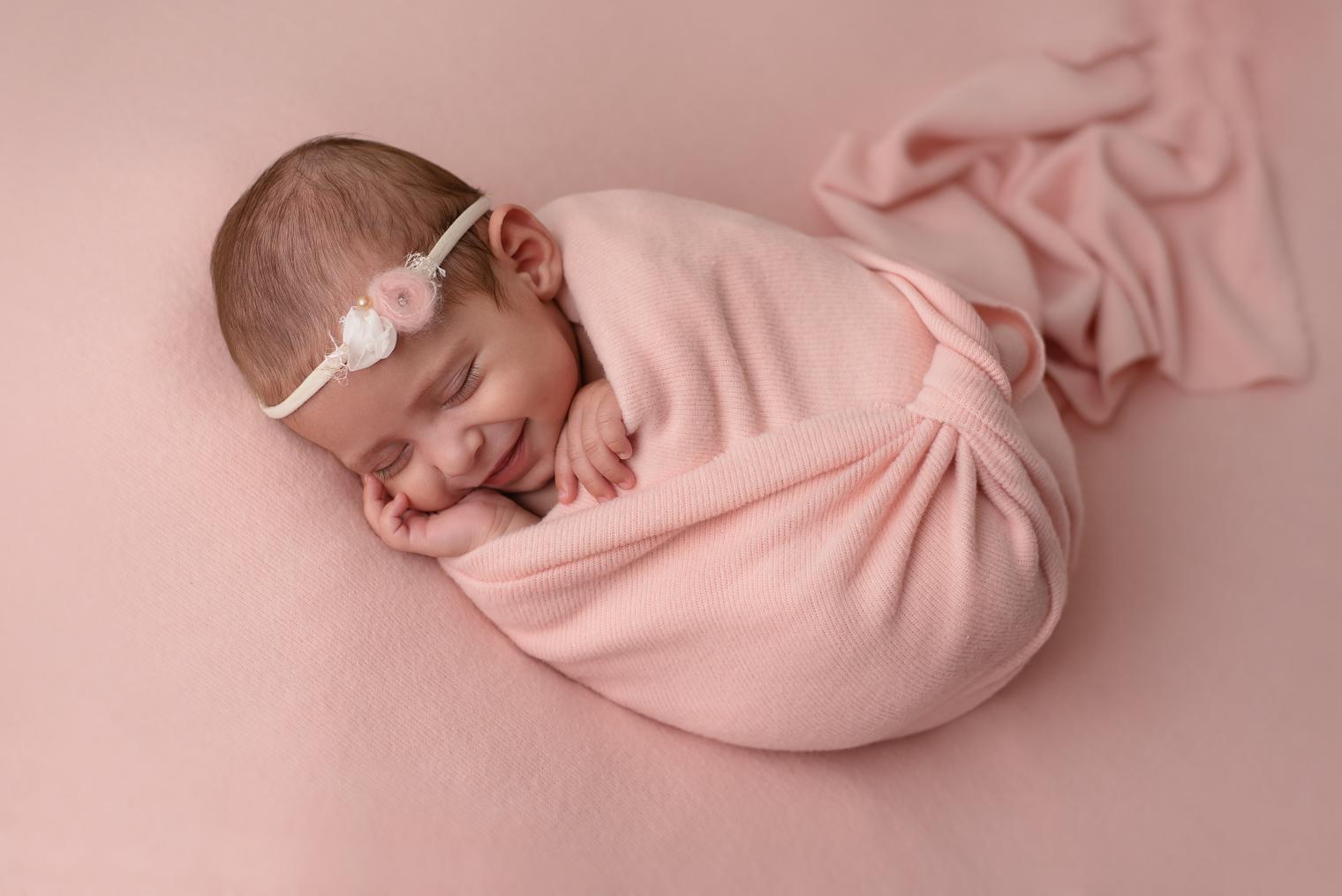 Bébé fille qui sourit, emmaillotée dans un tissu rose avec un bandeau rose et blanc