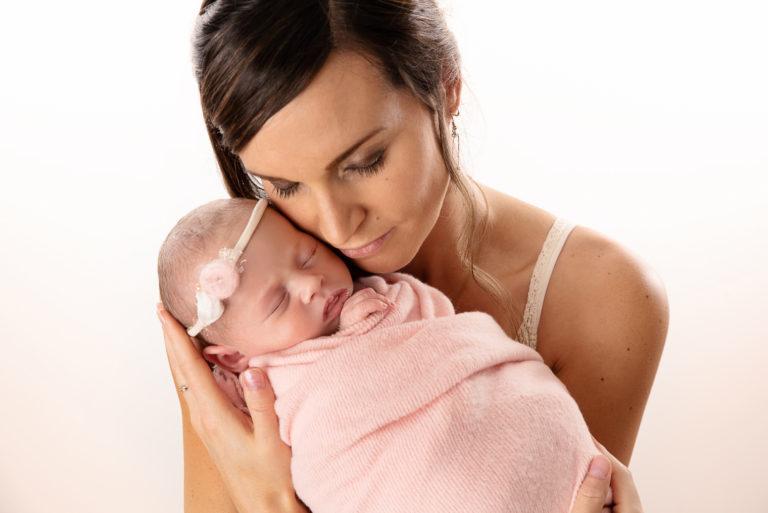 Nouveau-né fille endormie et emmaillotée dans un tissu rose, elle est dans les bras de sa maman