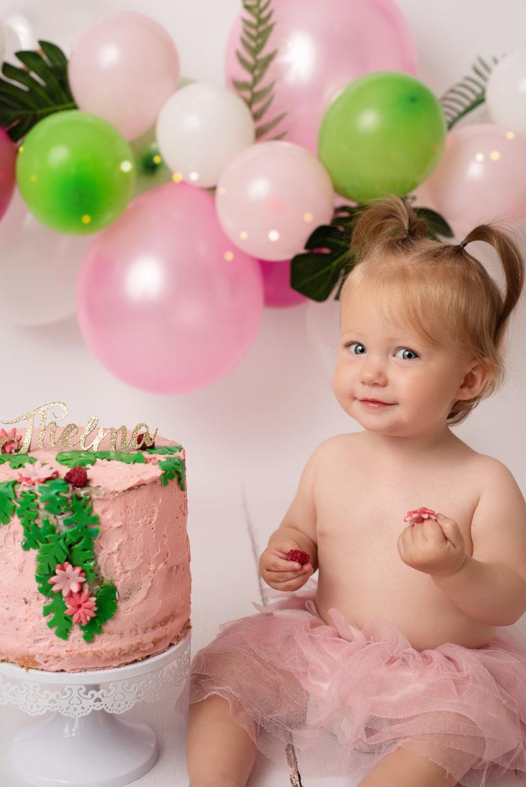 Petite fille d'un an avec un regard malicieux et des framboises dans les mains