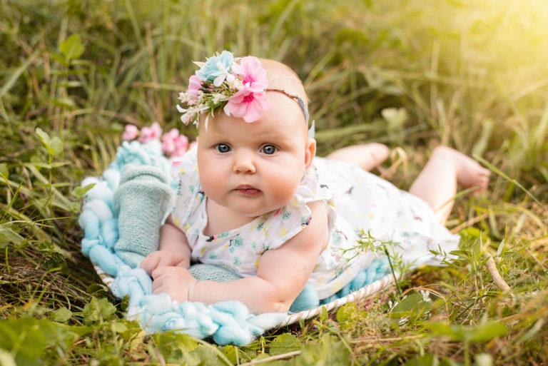 Bébé fille avec une robe à fleurs et un bandeau assorti, allongé sur le ventre sur une couverture en laine bleue posée dans l'herbe