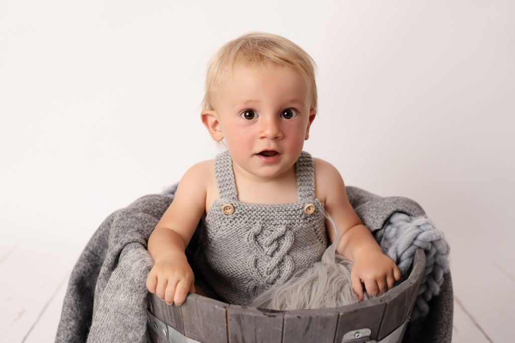 Bébé garçon habillé avec une barboteuse grise en tricot, assis dans un pot de fleur en bois et rempli de couvertures en laine