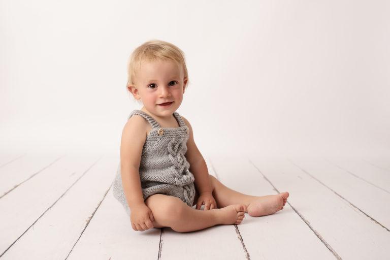 Bébé garçon qui sourit, habillé avec une barboteuse grise en tricot, assis sur un parquet blanc