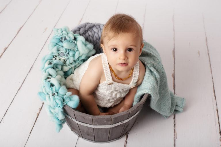 Bébé garçon habillé avec une barboteuse blanche en tricot, assis dans un pot de fleur en bois gris rempli de couvertures en laine bleue