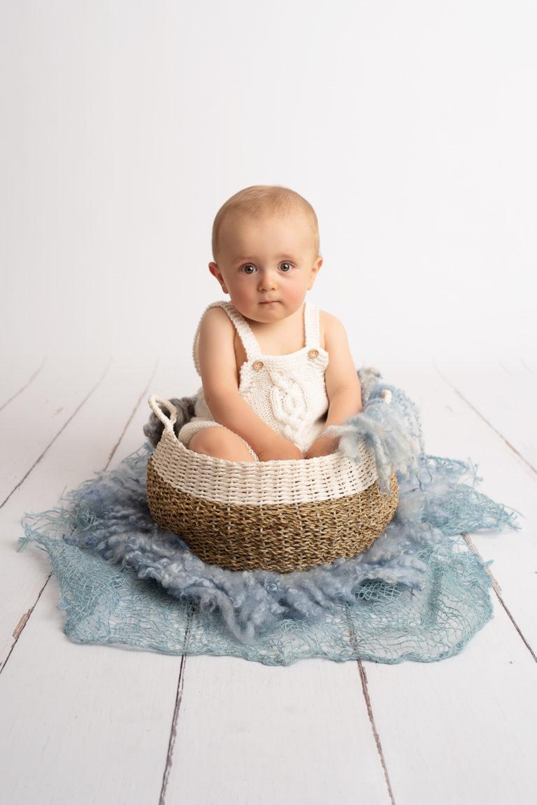 Bébé garçon habillé avec une barboteuse blanche en tricot, assis dans un panier en osier