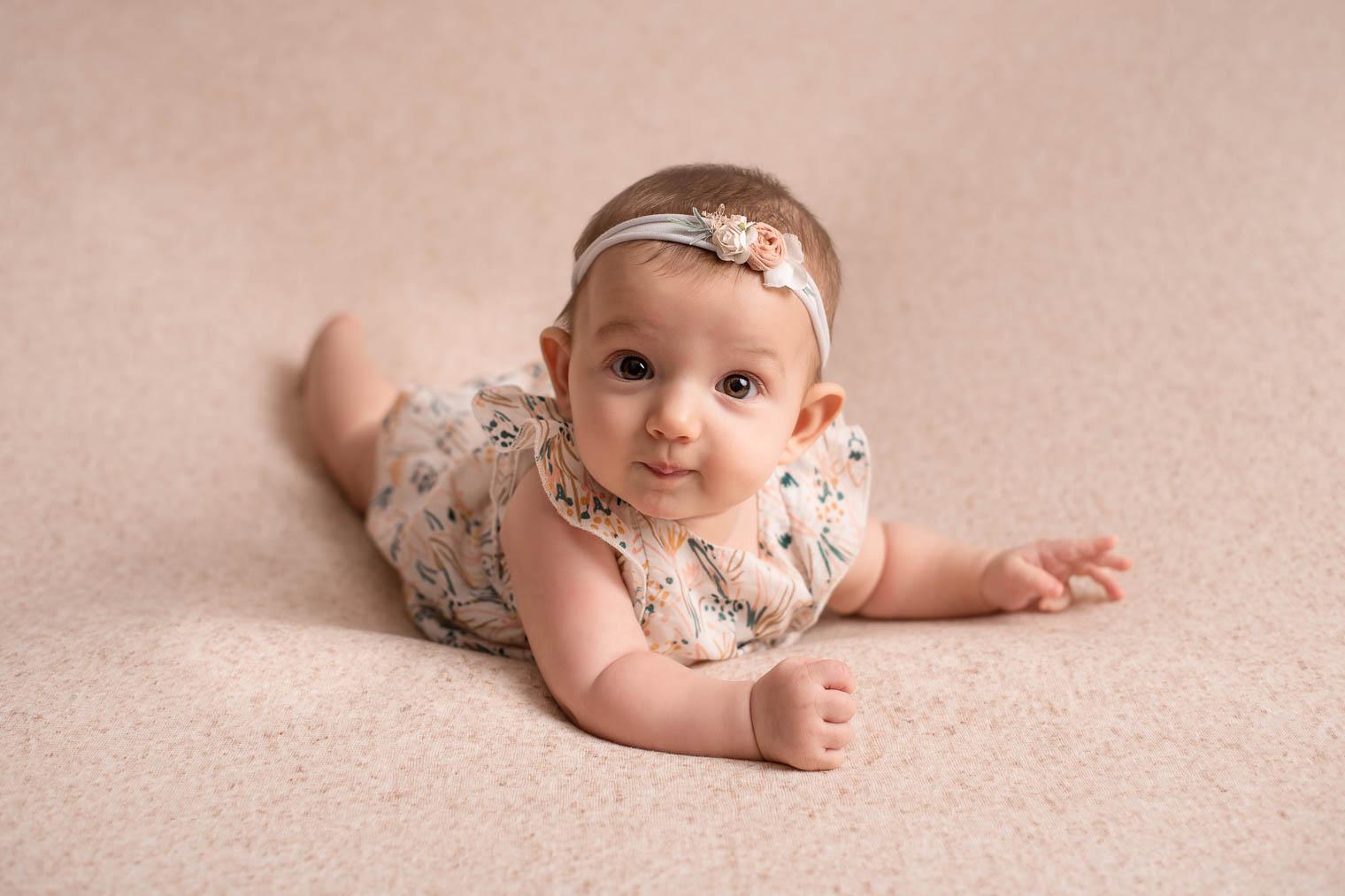 Bébé fille avec une robe à fleurs et un bandeau assorti, allongé sur le ventre sur un tissu beige chiné