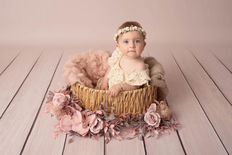 Bébé fille avec une robe en crochet écru et une couronne de fleurs, assises dans un panier en osier avec une couverture en laine rose