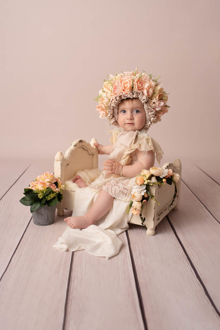 Bébé fille avec une robe en dentelle et un bonnet fleuri assise dans un petit lit
