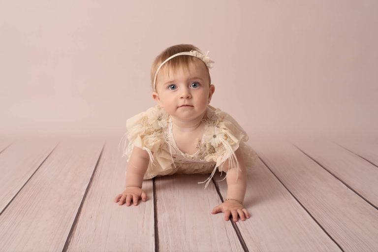 Bébé fille avec une robe en dentelle et un bandeau assorti, elle fait du quatre pattes