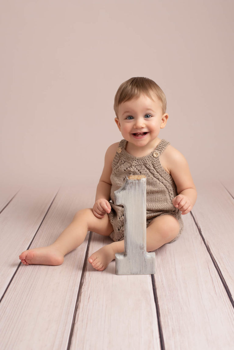 Bébé garçon qui sourit, habillé avec une barboteuse beige en tricot, assis sur un parquet beige avec un chiffre un en bois devant lui