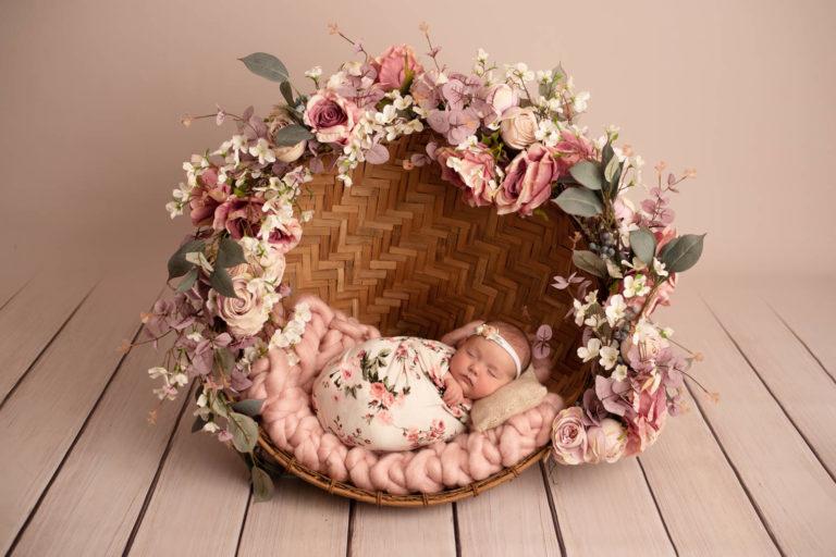 Nouveau-né fille emmaillotée dans une couverture crème avec des fleurs roses, dort dans un abat-jour recouvert d'une guirlande de fleurs