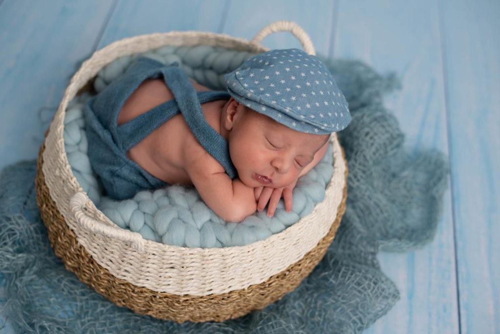 Nouveau-né garçon allongé sur le ventre dans un panier, sur une couverture en laine bleu, il porte une salopette et un béret bleu avec des petites étoiles blanche