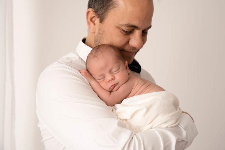 Papa habillé avec une chemise blanche, qui porte son nouveau-né dans les bras et le regarde avec un sourire de fierté