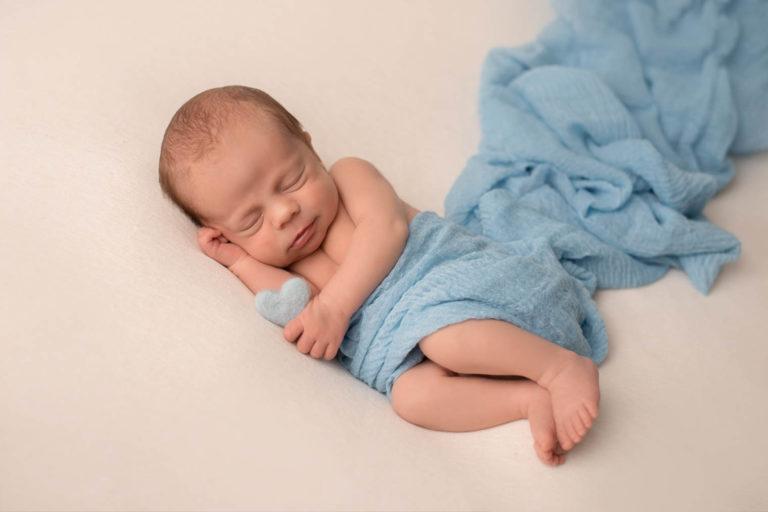 Nouveau-né garçon allongé sur le côté sur un tissu couleur crème avec un coeur bleu dans la main et un tissu bleu comme couverture