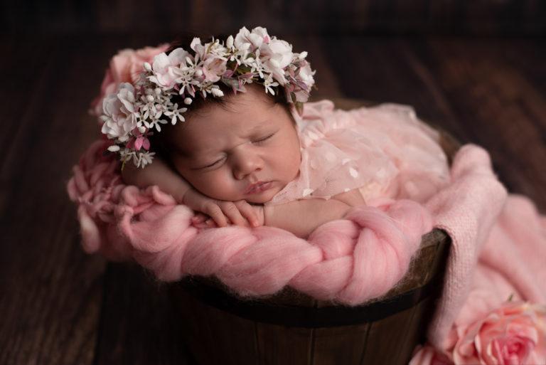 Nouveau-né fille paisiblement endormie avec une robe en tulle rose dans un seau en bois