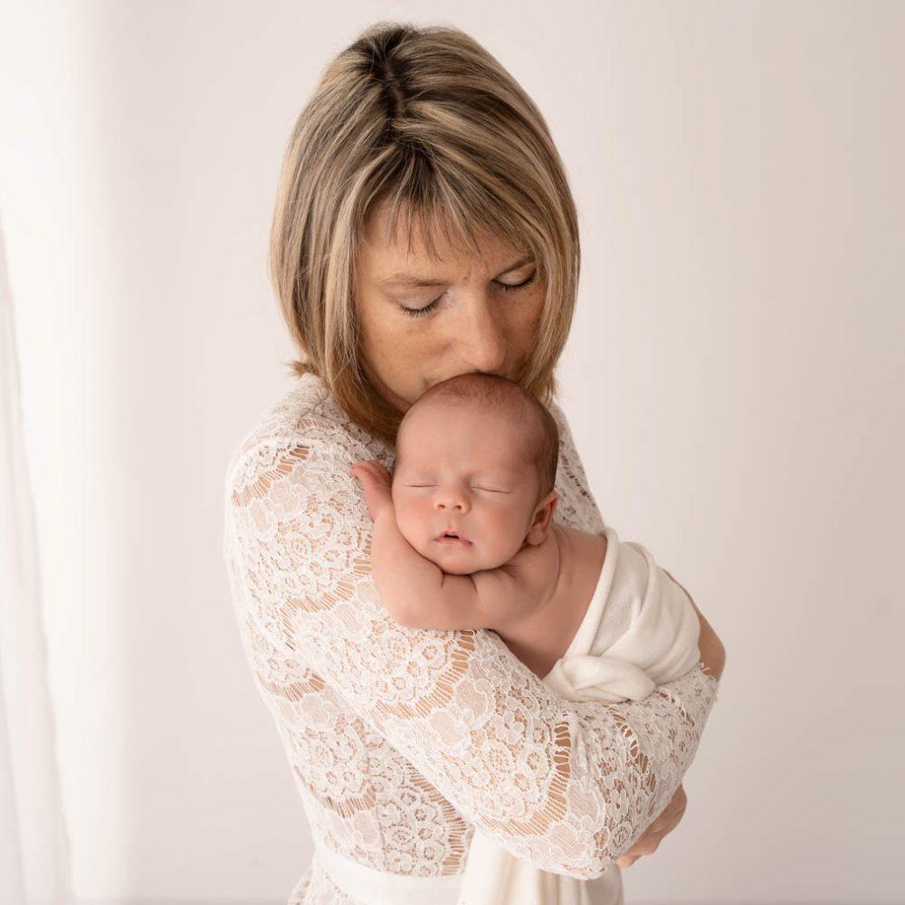 Maman habillée d'une robe en dentelle, qui porte son nouveau-né dans les bras et lui fait un bisous sur le dessus de la tête