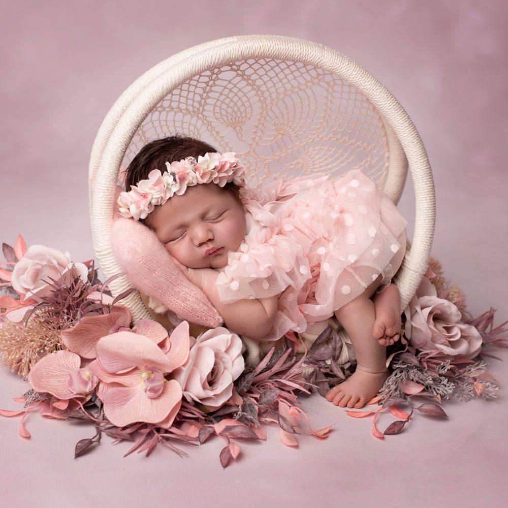 Nouveau-né fille paisiblement endormie avec une robe en tulle rose entourée de fleurs